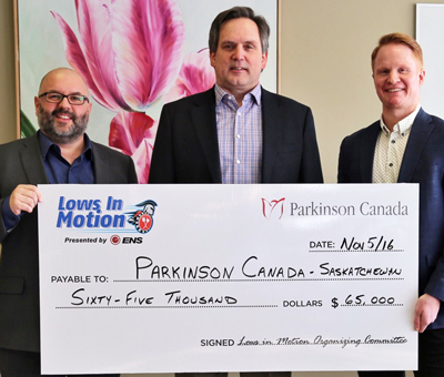 Travis Low, right, presents the 2016 proceeds to Marlin Stangeland and Todd MacPherson, Parkinson Canada.