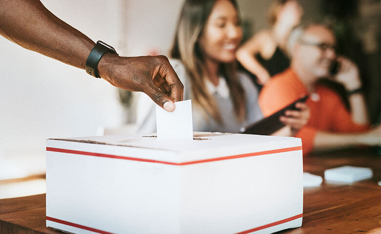 Hand submitting their vote into a ballot box
