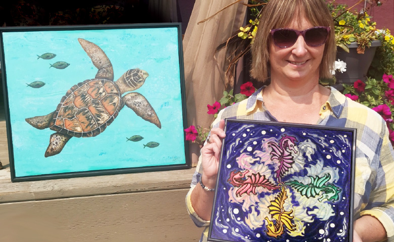 Artist Janice Horn with two of her paintings